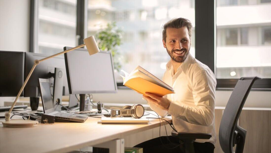 Photo of a man smiling and looking off into the distance away from the desk where his computer screens and lap are. Clearly, the man is procrastinating instead of focusing on work. Therapy in Ballard with a trained Seattle counselor can help him learn to be more productive.